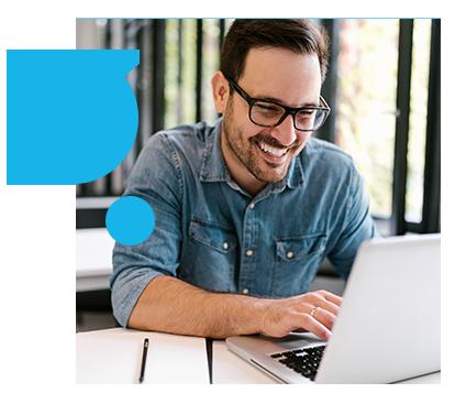 man smiling working on laptop